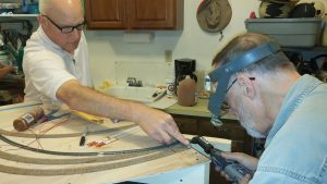 Brian and Mark are either grinding the end of a rail or Mark is giving Brian a manicure with a Dremel...